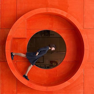 Woman in black dress in front of an orange facade
