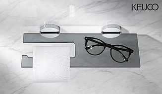 Toilet paper holder with toilet paper, next to it are black glasses