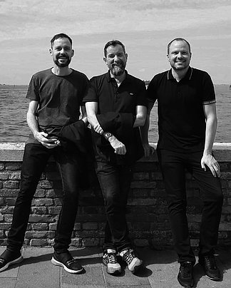 Three men are standing in front of a wall and in the background is the sea