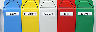 Coloured recycling bins marked with paper, plastic, glas, etc.