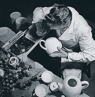 Porcelain worker at work, drawing decor lines on a tea pot