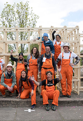 A big Group in orange colored working clothes standing in front of a wooden construct